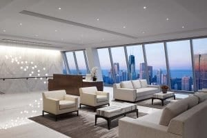Reception and lounge area with Chicago skyline views through floor-to-ceiling windows at Balyasny Asset Management's West Lake Street office built by J.T. Magen.