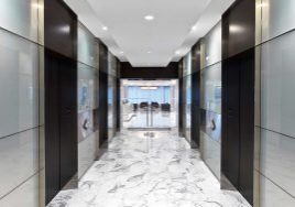 Marble tiled corridor with elevator entrances at the headquarters of an institutional investment management firm built by J.T. Magen on Madison Avenue, New York.